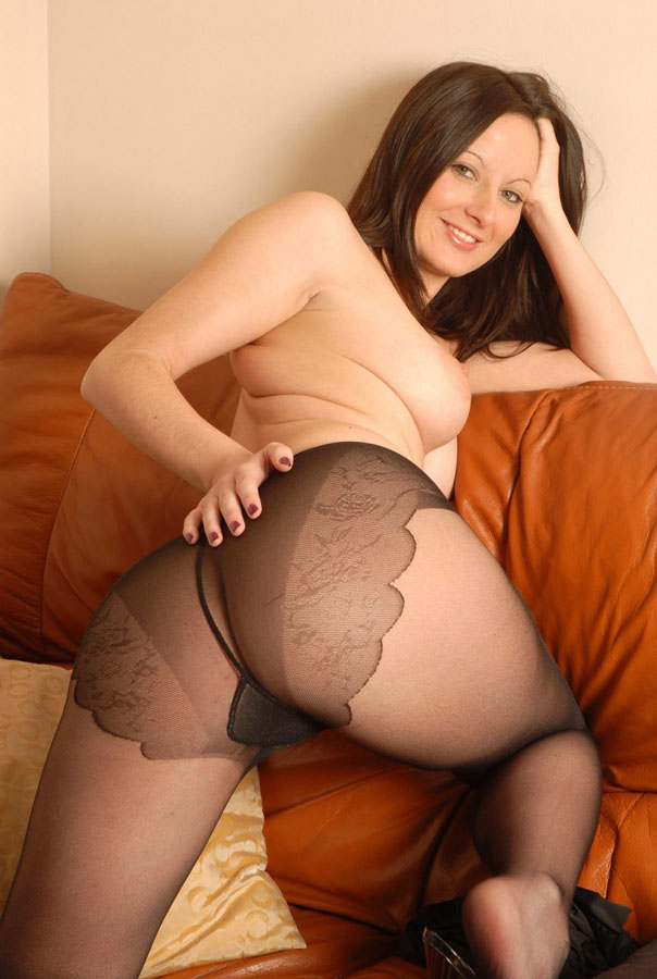Horny babe in black pantyhose on the couch